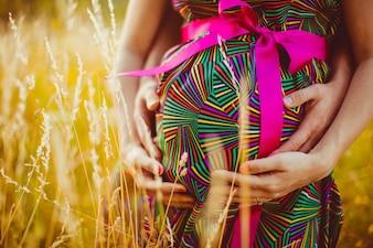 Mujer embarazada con su marido abrazando su barriga