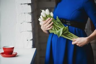 Mujer embarazada con unas flores blancas