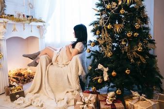 Mujer embarazada en sillón en tiempo de Navidad