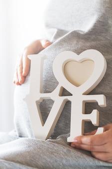 Mujer embarazada sujetando la palabra  love