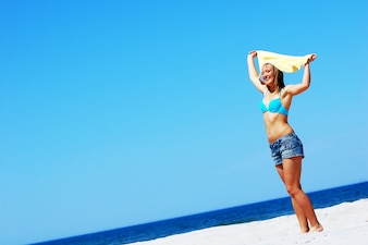 Mujer en bikini divirtiéndose en la playa