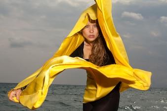 Mujer en la playa con pañuelo amarillo