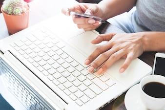 Mujer en ropa casual con ordenador portátil con tarjeta de crédito, compras en línea en casa