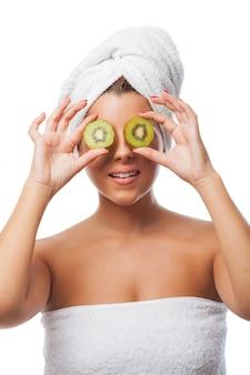 Mujer en toalla con kiwis en sus ojos