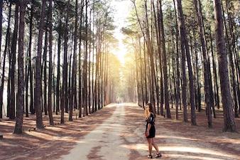 Mujer en un camino de tierra con árboles a los lados