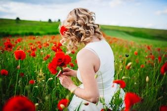 Mujer en un campo de flores rojas