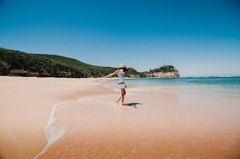 Mujer en vestido que goza de la playa en Australia.