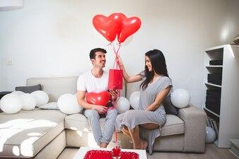 Mujer entregando a su novio globos y una bolsa roja