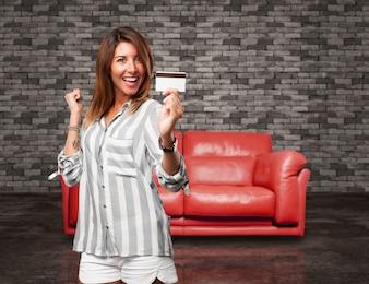 Mujer entusiasmada sujetando una tarjeta de crédito