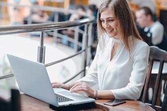 Mujer escribiendo en un portátil en una cafetería