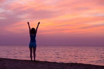 Mujer estirando sus brazos al anochecer