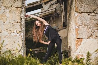Mujer, estirar, abandonado, edificio