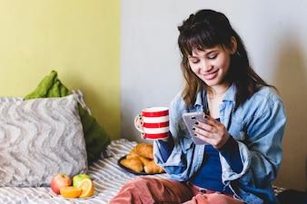 Mujer feliz con bebidas y teléfono