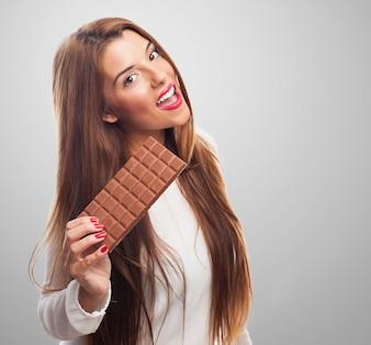 Mujer feliz con la barra de chocolate con leche