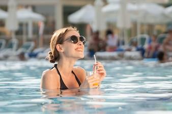 Mujer feliz disfrutando de una bebida en la piscina