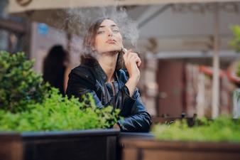 Mujer feliz fumando con un cigarrillo electrónico