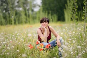 Mujer feliz sentada en medio del prado