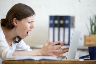 Mujer gritando al portátil