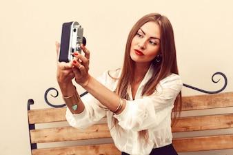 Mujer guapa jugando con su cámara vintage