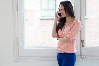 Mujer hablando por teléfono cerca de la ventana