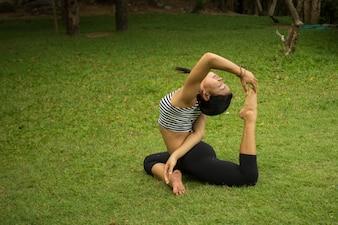 Mujer haciendo yoga sobre el césped