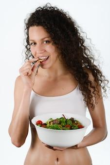 Mujer hambrienta comiendo una ensalada