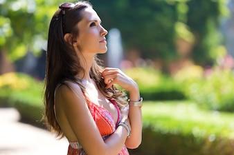 Mujer hermosa con el pelo oscuro y los ojos marrones que presentan en el jardín del verano.