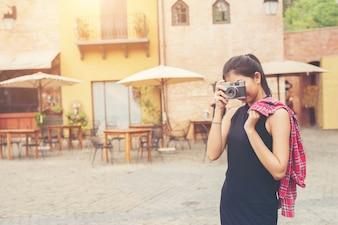 Mujer hermosa joven con la cámara retro, estilo retro de cosecha,