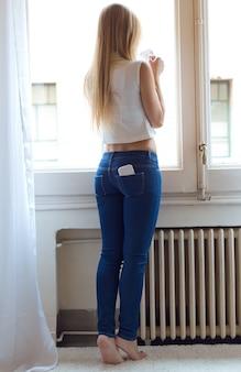 Mujer hermosa joven en el país con el teléfono móvil en bolsillo trasero.