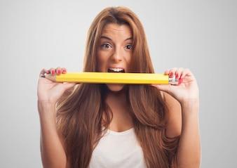 Mujer hermosa que come el lápiz grande.