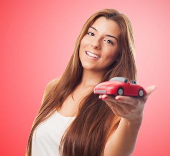 Mujer hermosa y coche de juguete.