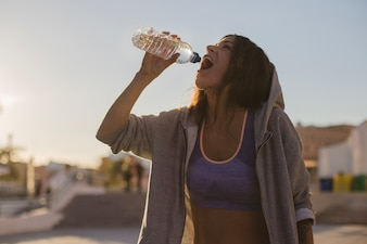 Mujer, hoodie, bebida, agua, posición, afuera