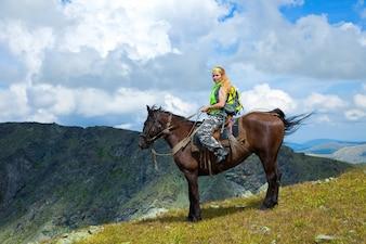 Mujer jinete a caballo en las montañas