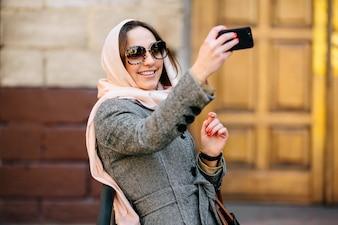 Mujer joven a la moda haciéndose una foto