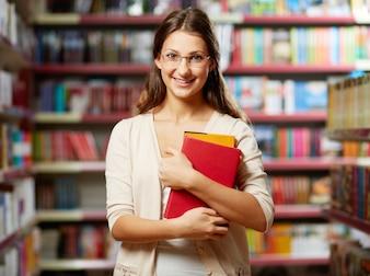 Mujer joven aguantando libros en una biblioteca