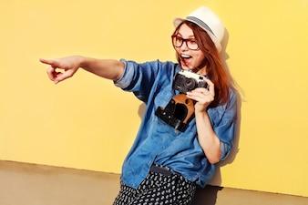Mujer joven alegre con cámara mostrando algo con su dedo
