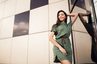 Mujer joven apoyada en un cristal de un edificio