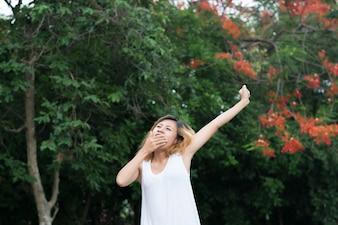 Mujer joven cansada estirando sus brazos