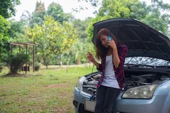 Mujer joven con el coche se descompone y ella está llamando a los servicios de emergencia.