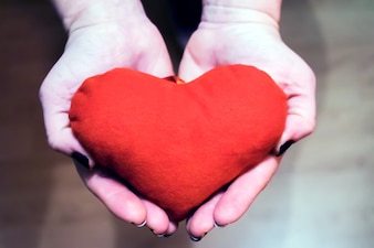 Mujer joven con el corazón rojo en la mano