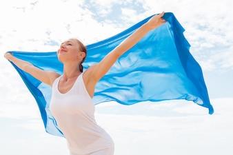 Mujer joven con la bufanda azul de vuelo