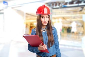 Mujer joven de moda que sostiene una carpeta de color rojo y que lleva un casco