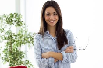 Mujer joven de negocios mirando la cámara en la oficina.