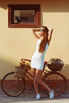 Mujer joven disfrutando del sol con su bicicleta