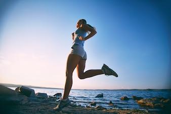 Mujer joven entrenando en la playa