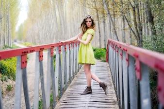 Mujer joven estilosa cruzando un puente