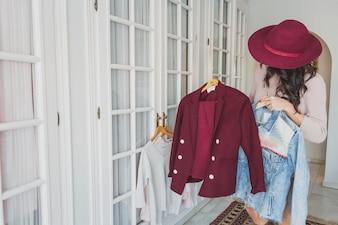 Mujer joven estilosa mirando un traje burdeos