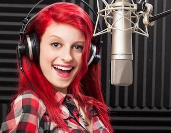 Mujer joven feliz en un estudio de música