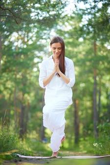 Mujer joven haciendo una clase de yoga en el parque