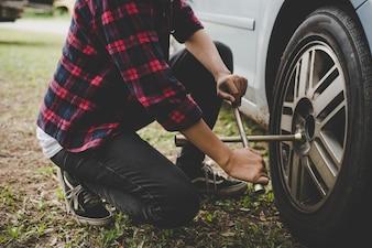 Mujer joven hipster comprobación de un neumático plano en su coche tratar de arreglar.